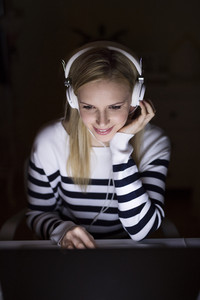 Young beautiful woman in striped sweater sitting at desk, looking at the screen of a laptop late at night, headphones on head.