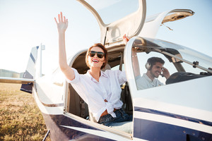 Young beautiful woman in sunglasses waving from the plane cabin after landing