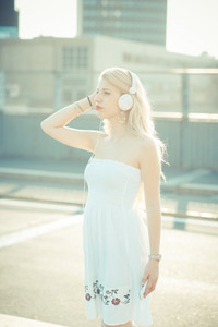 Young beautiful woman in the city back light listening music - enjoying, relaxing, music concept