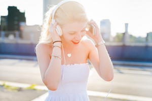 Young beautiful woman in the city back light listening music with smart phone hand hold - enjoying, relaxing, music concept