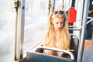 Young beautiful woman in the city travelling by bus - traveller, commuter, studying concept