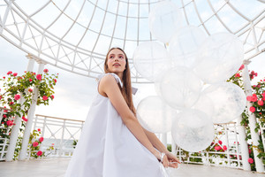 Young beautiful woman in white dress with balloons at the terrace outdoors