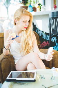 Young beautiful woman indoor eating ice cream using smart phone - technology, social network, refreshment concept