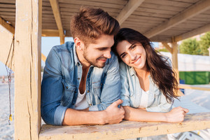 Young beautiful woman leaning on her boyfriend shoulder while standing at the wooden beach house