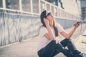 young beautiful woman listening music in the city