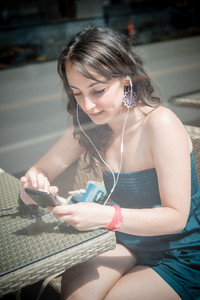 young beautiful woman listening to music at the coffee