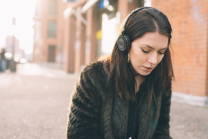 young beautiful woman listening to music with headphones in the city