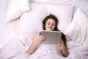 Young Beautiful Woman Lying On Bed And Holding Digital Tablet