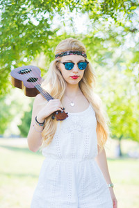 Young beautiful woman outdoor city park playing ukulele - musician, composer, busker concept