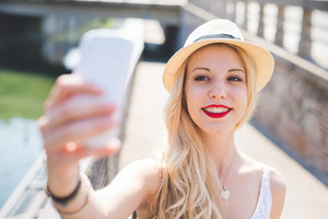 Young beautiful woman outdoor city taking selfie smiling with smart phone hand hold - social network, sharing, vanity concept
