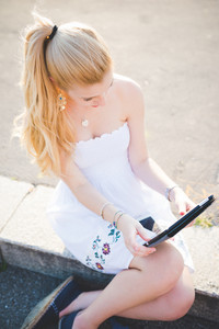 Young beautiful woman outdoor in the city back light using tablet - technology, small business, remote working concept