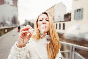 Young beautiful woman playing with bubble soap - happiness, cheerful, having fun concept