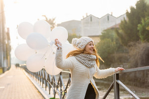 young beautiful woman playing with white baloon outdoor city - party, celebration, happiness concept