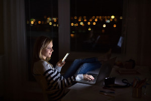 Young beautiful woman sitting at desk at night, holding smartphone, working on laptop at night.