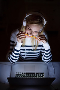 Young beautiful woman sitting at desk at night, looking at the screen of a laptop late at night, headphones on head.