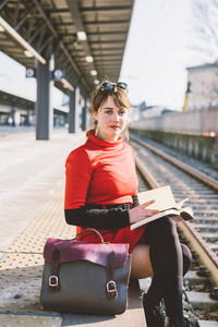 Young beautiful woman sitting on a platform in a train station reading a book, looking in camera - student, commuter, reading concept