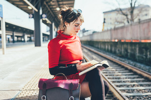 Young beautiful woman sitting on a platform in a train station reading a book- student, commuter, reading concept
