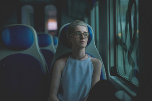 Young beautiful woman sitting on a train, looking out the window, pensive - serious, thoughtful, commuter concept