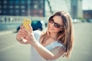 young beautiful woman taking selfie in the city