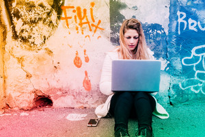 Young beautiful woman using computer sitting outdoor - small business, technology, student concept