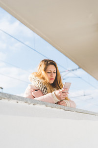 young beautiful woman using smart phone outdoor - technology, social network, internet concept