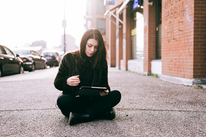 young beautiful woman using tablet in the city