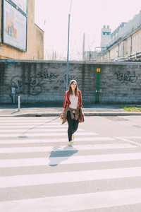 Young beautiful woman walking outdoor in the city - getting away from it all, city living, everyday life concept