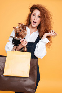 Young beautiful woman with little dog yorkshire terrier and shopping bags holding mobile phone isolated on orange