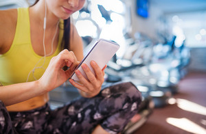 Young beautiful woman with smart phone in gym