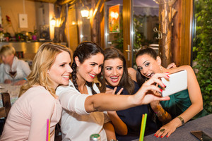 Young beautiful women taking selfie with smart phone in bar or club having fun
