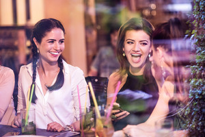 Young beautiful women with cocktails in bar or club, drinking, having fun