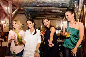 Young beautiful women with cocktails in bar or club having fun, dancing