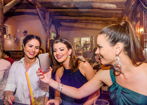 Young beautiful women with cocktails in bar or club talking, having fun, showing pictures on smart phone