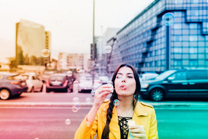 young beautiful yellow dressed vintage hipster woman outdoor in the street of the city playing with bubble soap - childhood, having fun, happiness concept