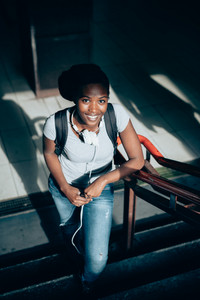 Young black beautiful woman walking upstairs from underground using smart phone hand hold - technology, social network, communication concept