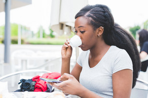 Young black woman having a cup of coffee outdoor in a bar, using a smart phone hand hold - relax, technology, social network concept