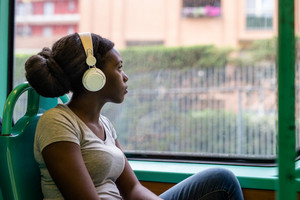 Young black woman listening music travelling by bus looking outdoor the window, pensive - thoughtful, thinking future, music concept