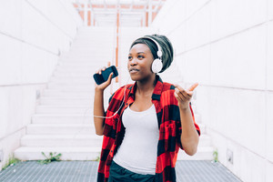 Young black woman listening music with headphones and smart phone hand hold dancing outdoor in the city, smiling - happiness, serene, technology concept