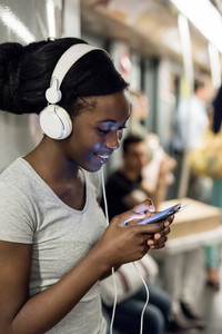 Young black woman listening music with headphones and using smart phone hand hold traveling in the underground, smiling - commuter, music, technology concept