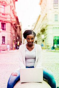 Young black woman using computer outdoor in the city sitting on a bench tapping the keyboard - business, student, technology concept