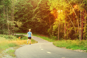 Young blond man jogging outside on a forest trail at sunset