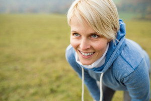 Young blond woman in blue sweatshirt with hood, breathing hard after running outside in sunny nature