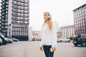 Young blonde beautiful woman listening music with head phones and smart phone hand hold - music, technology, relaxing concept