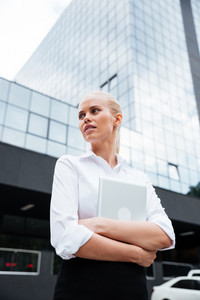 Young blonde business woman with tablet standing near her office outdoors