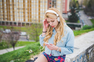 Young blonde caucasian girl listening music with headphones and smart phone hand hold in the suburbs - technology, music, relax concept