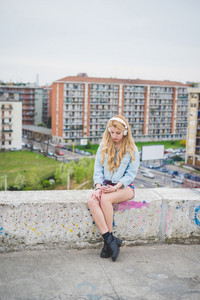 Young blonde caucasian girl listening music with headphones in the suburbs, sitting on a small wall with city in background, looking down the screen, pensive - technology, music, relax concept