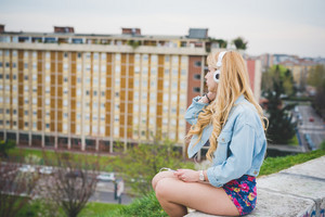 Young blonde caucasian girl listening music with headphones in the suburbs, sitting on a small wall with city in background, overlooking, pensive - technology, music, relax concept