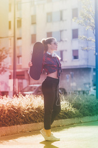 Young blonde caucasian skater woman posing outdoor in back light holding skateboard - sportive, skater, rebel concept