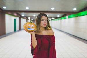 Young blonde caucasian woman in the underground holding an halloween lightning pumpkin - carnival, halloween, creepy concept