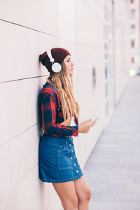 Young blonde caucasian woman outdoor in the city leaning on a wall listening music with smart phone hand hold - music, relaxing, technology concept